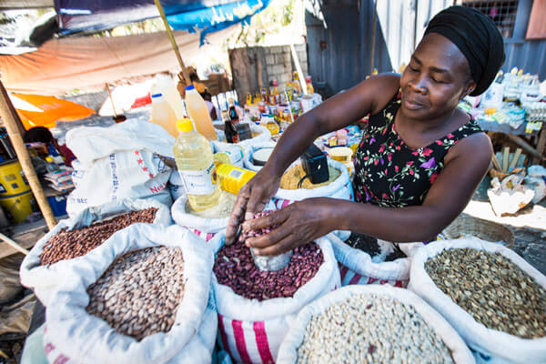 Dieula Basile fills a cupped with dried beans at her market stall
