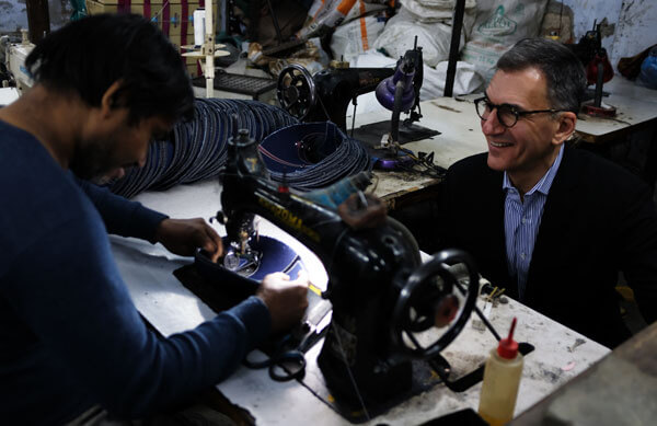 Michael Schlein sits across from a client of Aye Finance as the client uses a sewing machine.