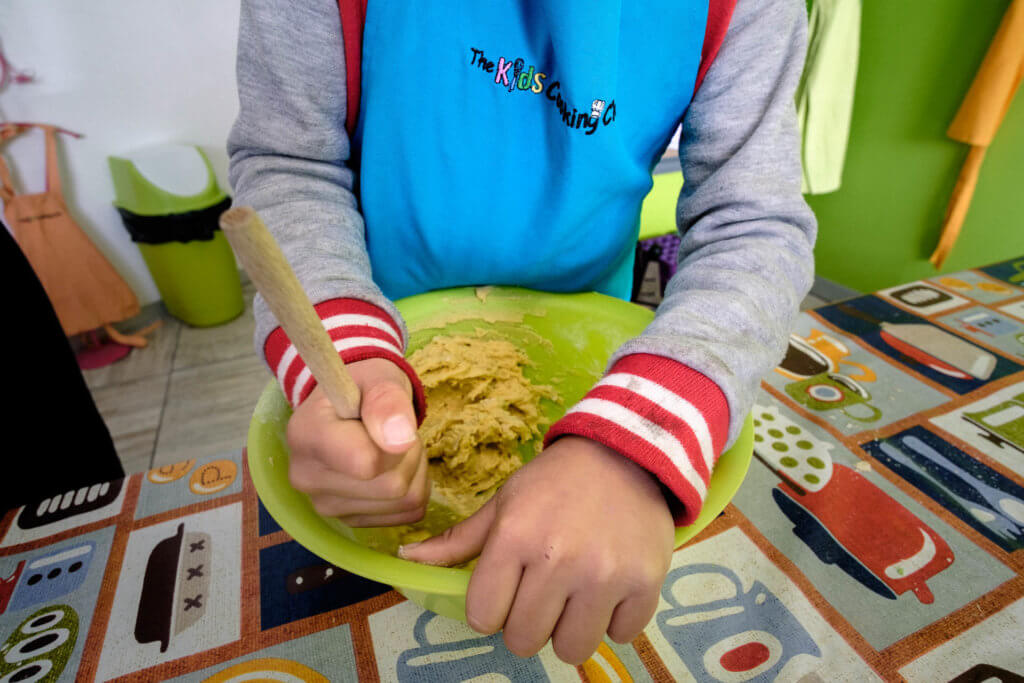 Child at Kids Cooking School mixing food in a bowl