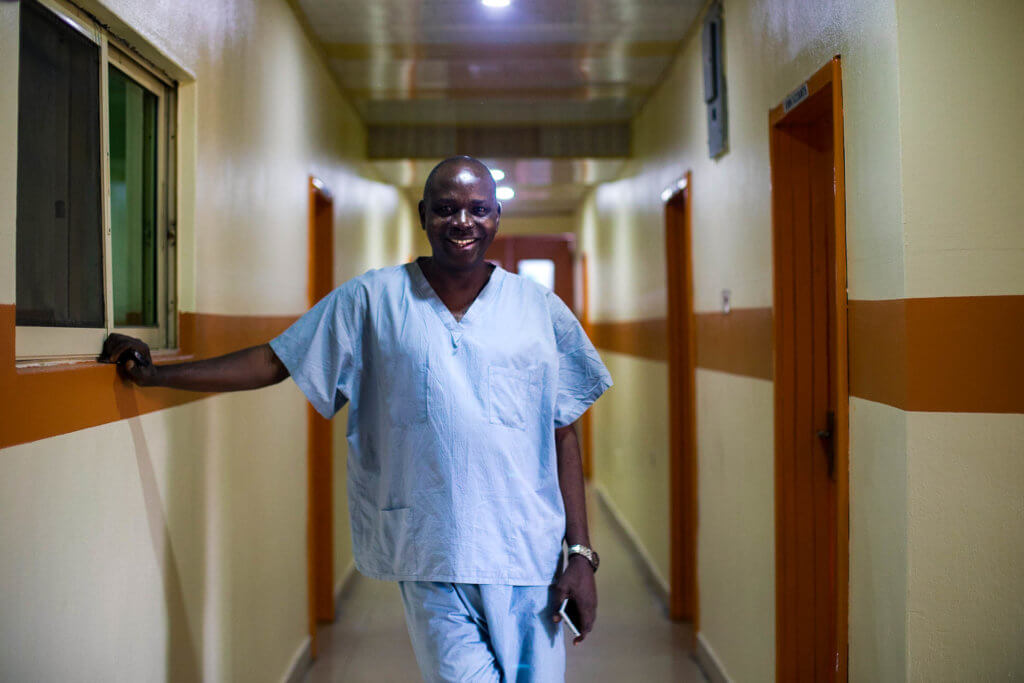 Dr. Akinpelu smiles in the halls of his clinic